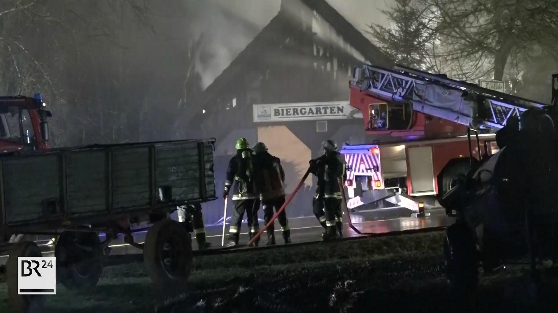 """Feuerwehrleute bei der Arbeit. Im Hintergrund die durch Brand zerstörte Gaststätte """"Zur Maut""""."""