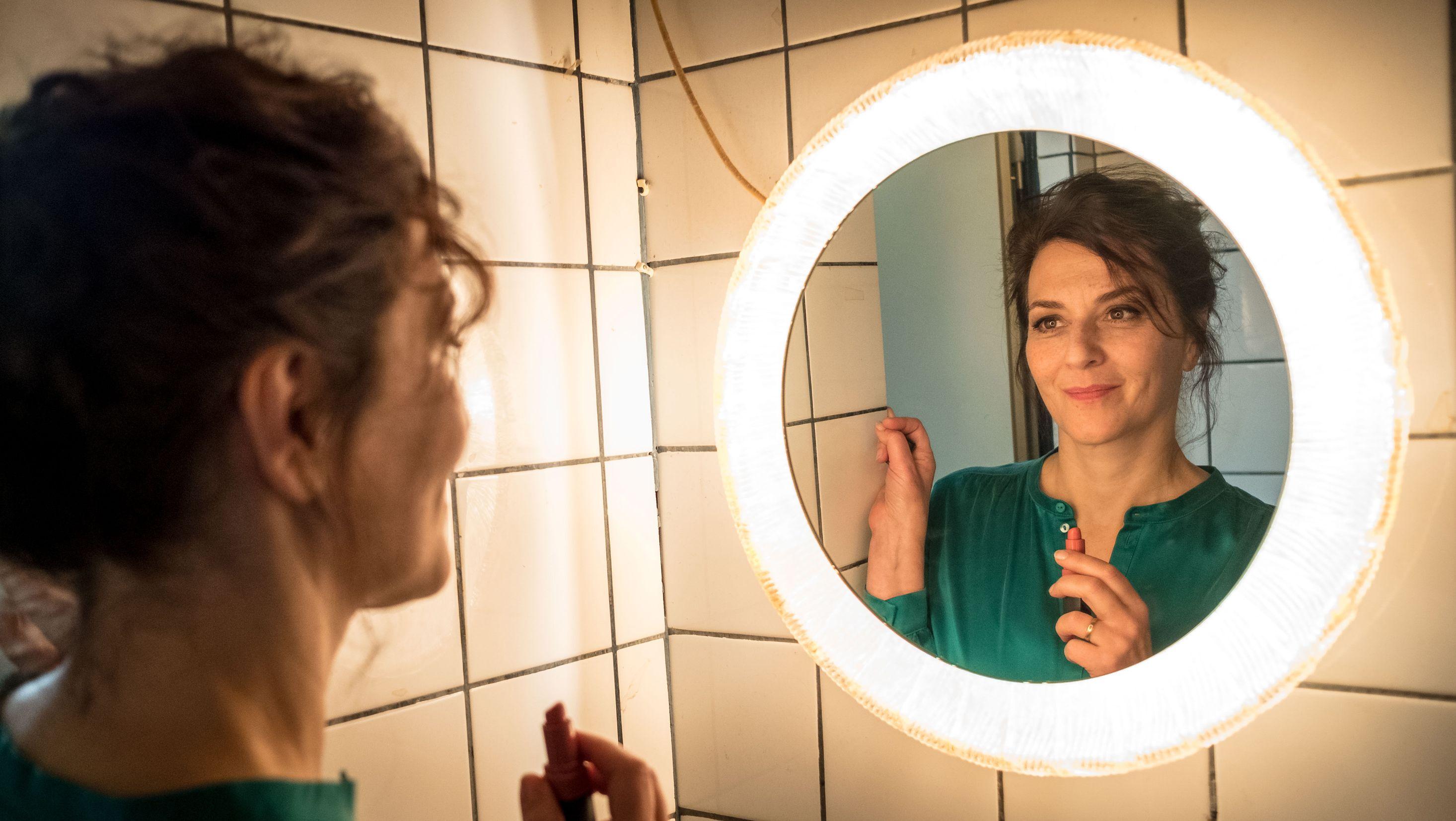 Martina Gedeck steht mit einem Lippenstift in der Hand vor einem Badezimmerspiegel