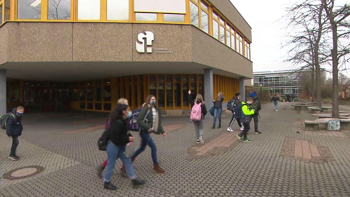 Schülerinnen und Schüler mit Masken vor einer Schule