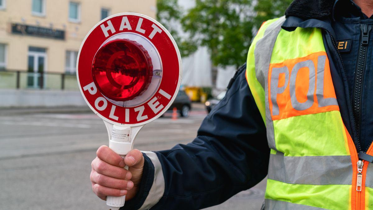 Beamter mit Polizeikelle in der Hand (Symbolbild)
