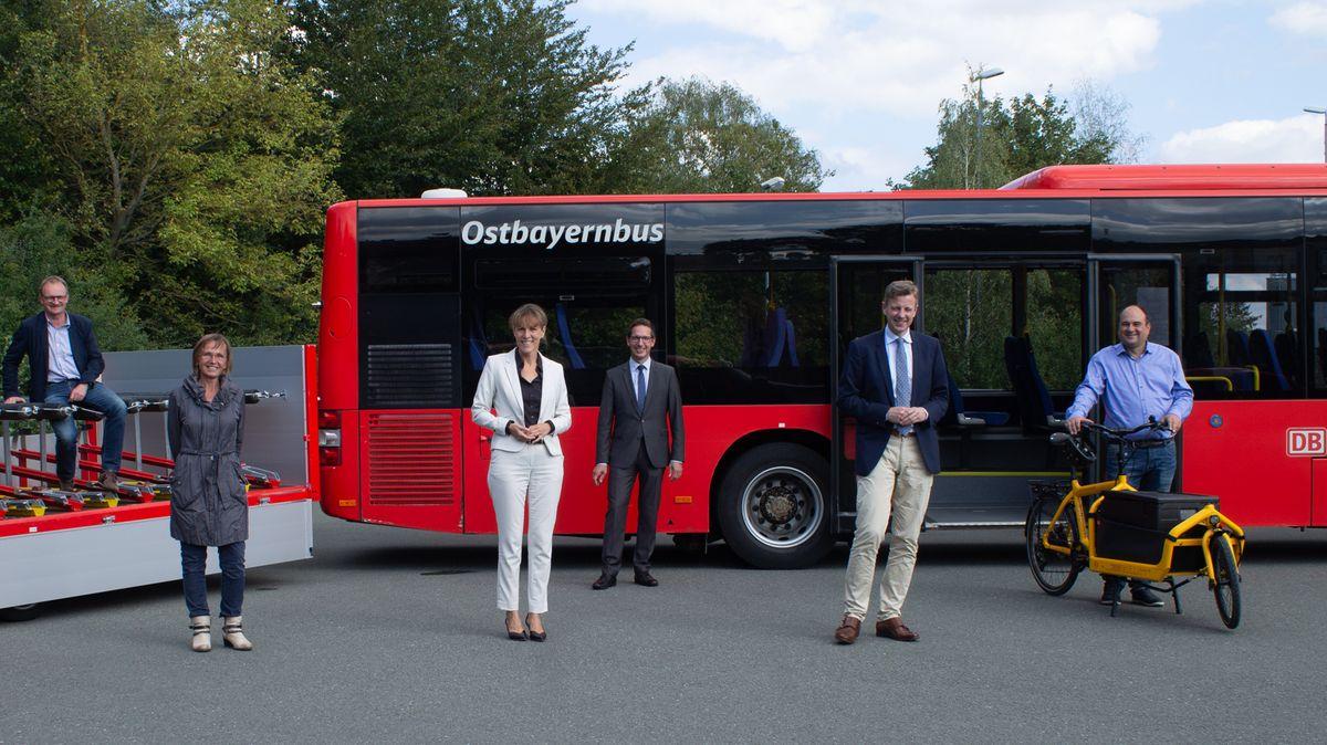 Sechs Menschen stehen vor einem Omnibus.