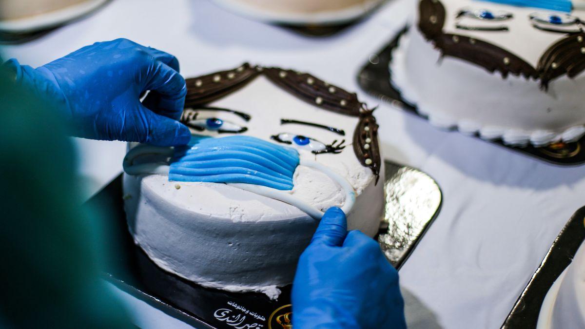Ein Konditor versieht eine fertige Torte mit einem aus Backwerk nachgebildeten Mundschutz