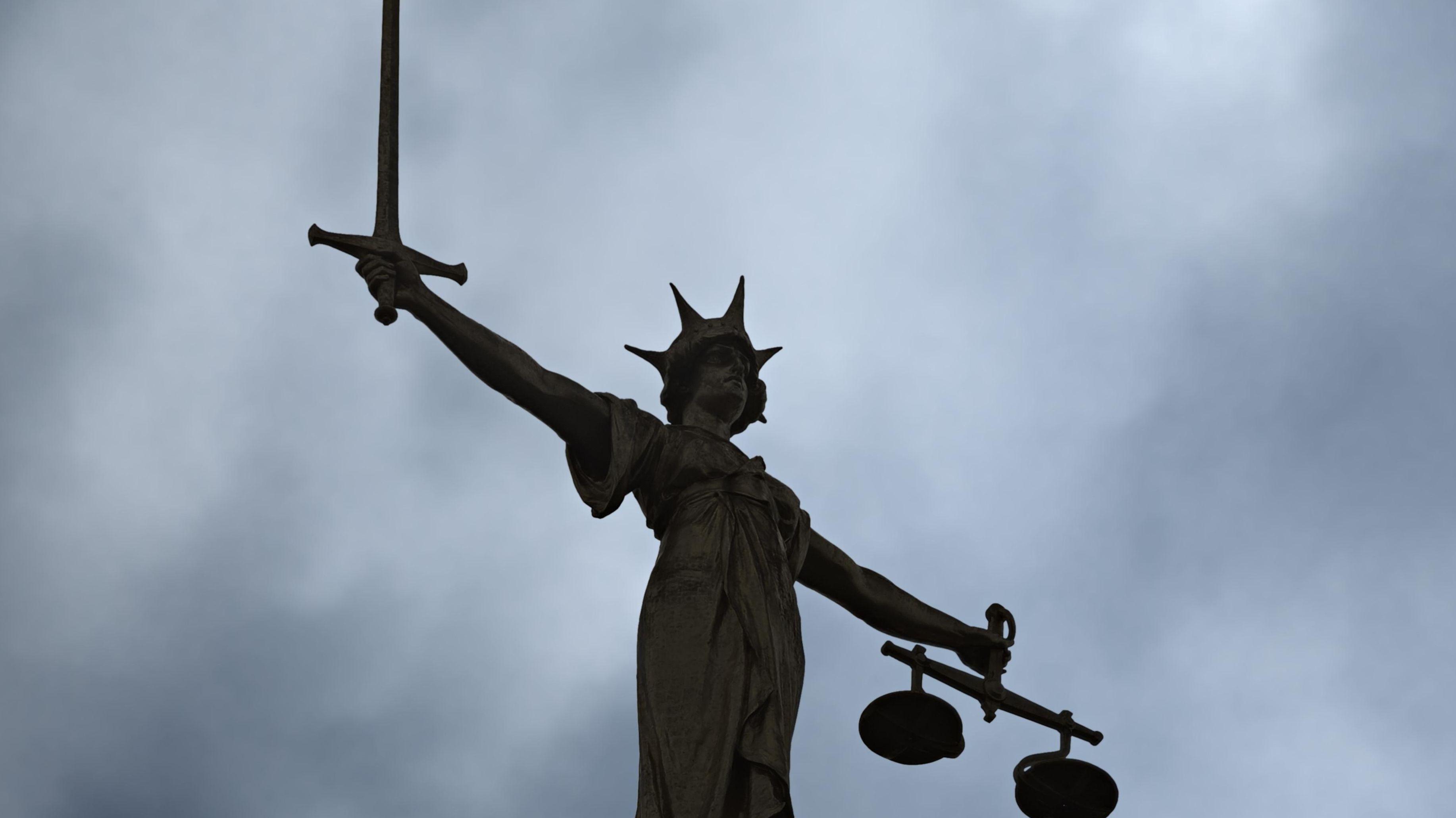 Statue der Justitia vor dunklem Himmel