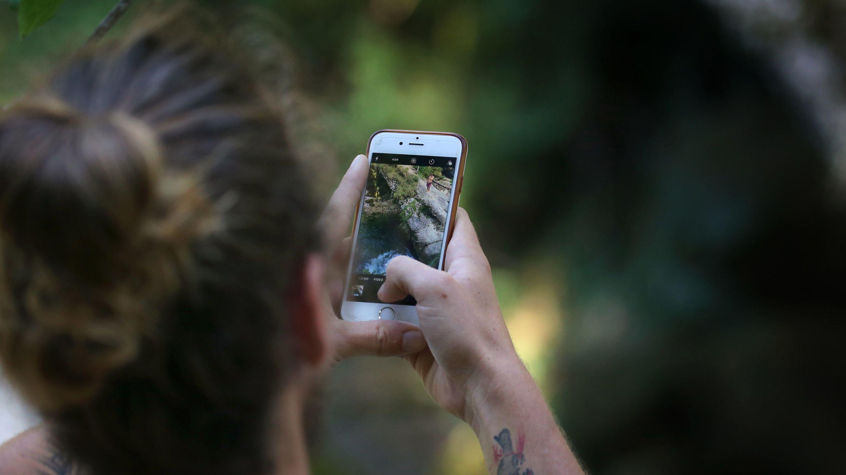 Ein junger Mann nimmt den Sprung zweier Frauen, in eine sechs Meter tiefer gelegene Gumpe, mit einem Smartphone auf.