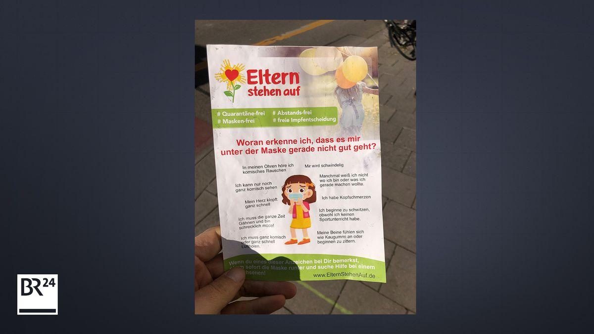 Ein Flyer der Initiative #Elternstehenauf wird in München verteilt.