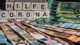 Coronahilfe und Geld auf dem Tisch   Bild:pa/Fotostand/K. Schmitt