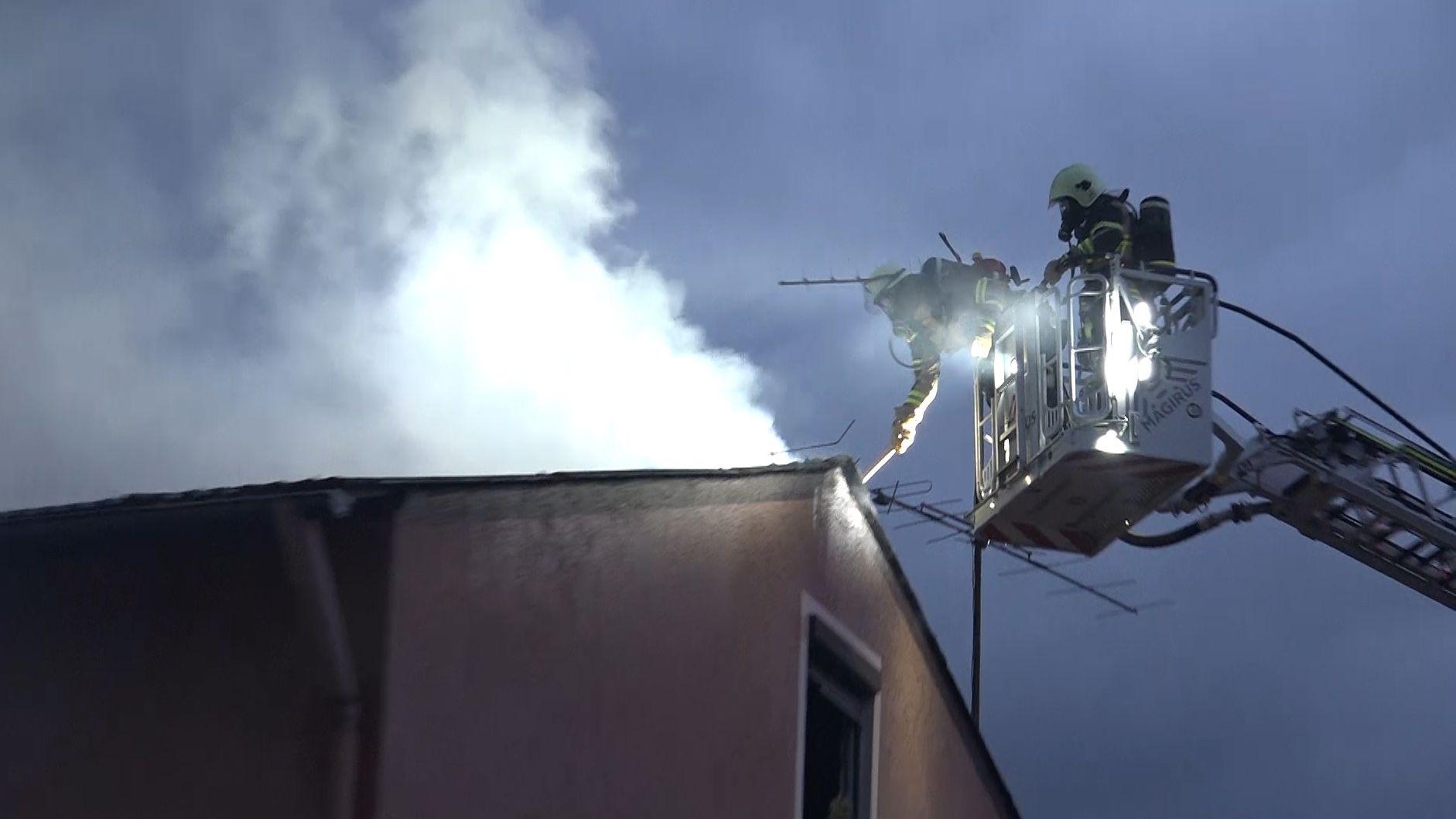 Einsatzkräfte auf einer Drehleiter am rauchenden Dach