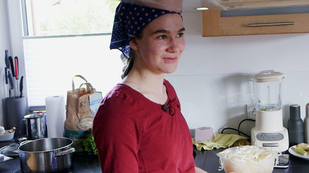 Dorfhelferin Dina Haas trägt ein Kopftuch und steht in der Küche einer Familie, bei der sie aushilft, zwischen Mixer und Kochtopf. Szene aus dem Beitrag im BR Fernsehen.