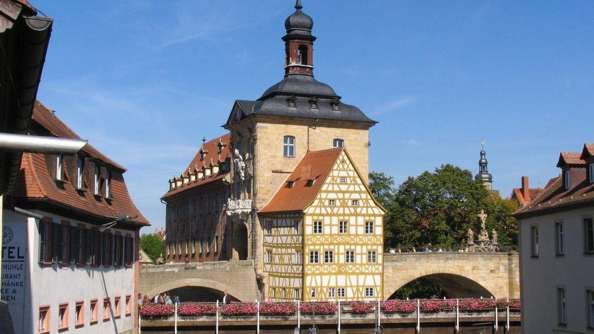 Blick auf eine Brücke mit zwei Bögen, an der ein Fachwerkhaus gebaut ist, dahinter ein Turm