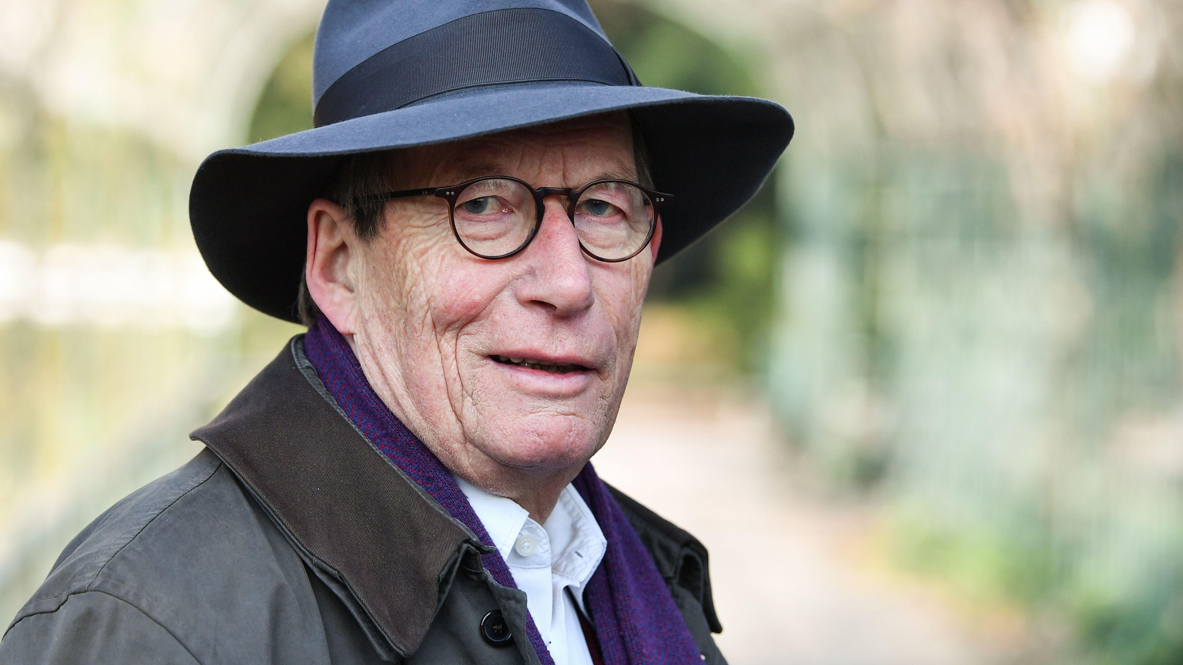 Friedrich Christian Delius blickt, mit Hut im Freien stehend, in die Kamera