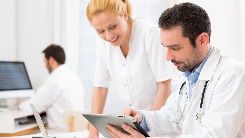Zwei Mitarbeiter im Krankenhaus sehen sich einen Tablet-Bildschirm an
