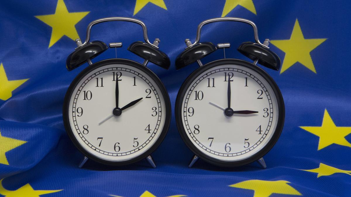 Zwei Wecker mit Winterzeit und Sommerzeit auf einer EU-Fahne