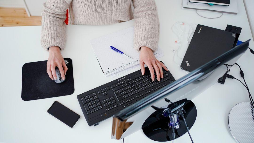 Eine Frau arbeitet in ihrer Wohnung vor einem Computer an einem Stehtisch