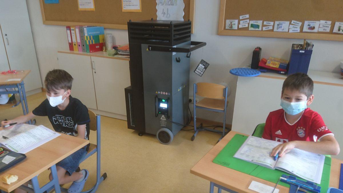 Hinter zwei Schülern, die mit Maske an ihren Schultischen sitzen,  steht ein schwarzer Kasten im Klassenzimmer - ein Luftreinigungsgerät.