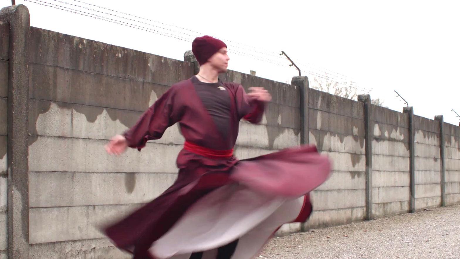 Ein Sufi tanzt vor der Mauer des Konzentrationslagers in Dachau