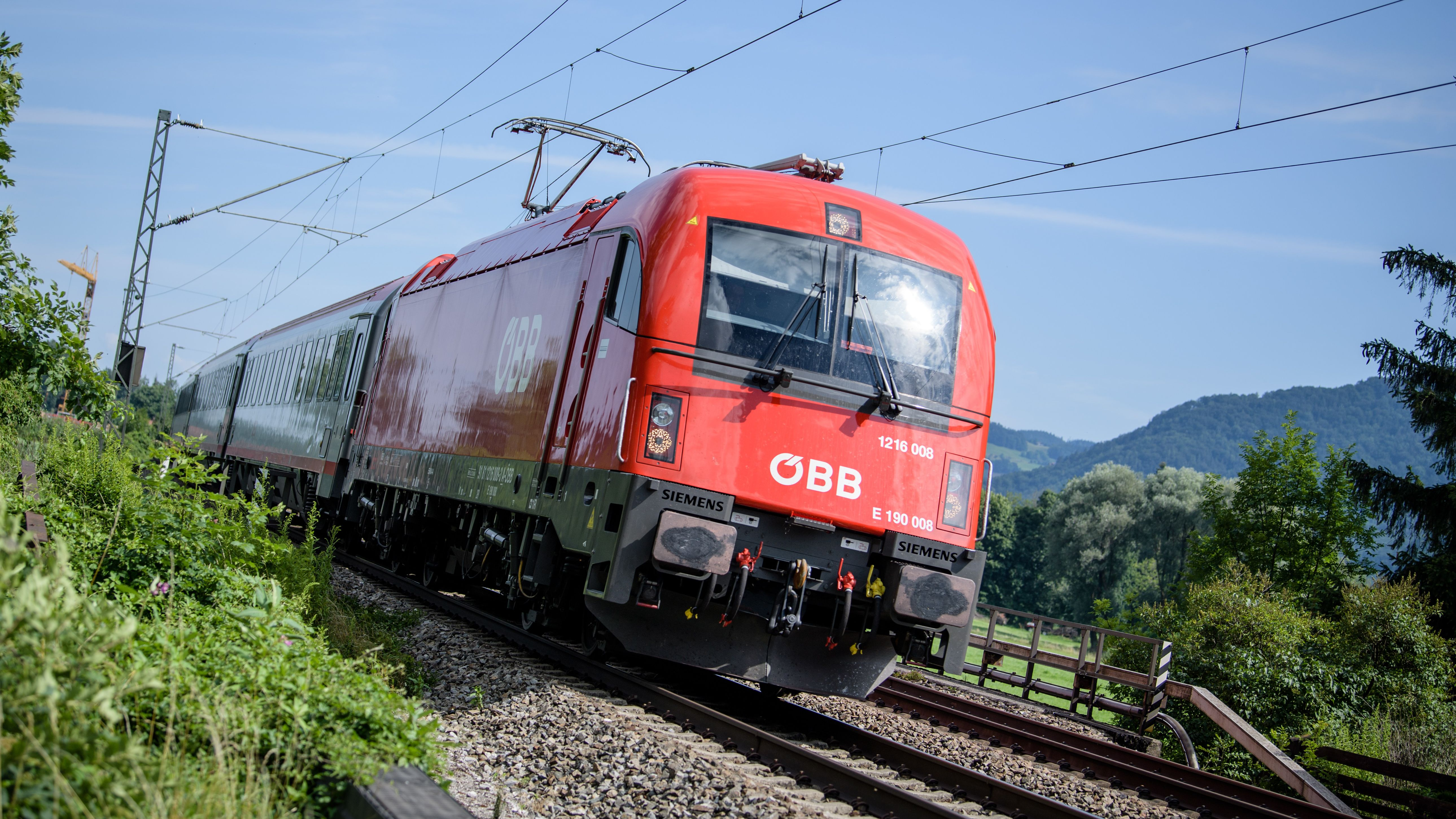 Ein Zug der Österreichischen Bundesbahnen (ÖBB) fährt über die Gleise der Bahntrasse durch das Inntal zwischen Rosenheim und Kufstein