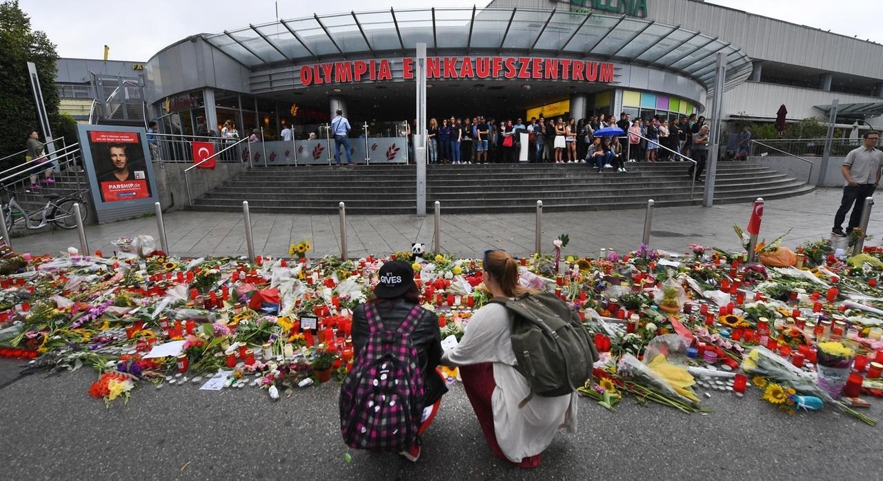 ARCHIV - 25.07.2016, Bayern, München: Blumen und Kerzen liegen vor dem Haupteingang des Olympia-Einkaufszentrums (OEZ). Drei Tage zuvor hatte dort ein 18-Jähriger neun Menschen erschossen und sich danach selbst getötet. Sky Deutschland arbeitet die Geschehnisse nun in einer Dokumentation auf. Drehstart ist im Sommer. (zu dpa «Sky dreht Dokumentation zu Münchner OEZ-Attentat») Foto: Peter Kneffel/dpa +++ dpa-Bildfunk +++