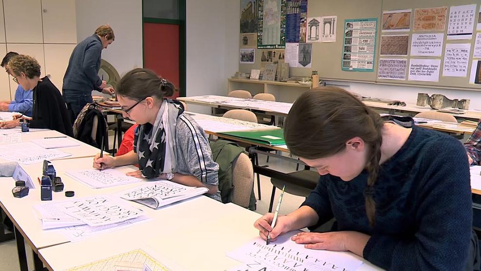 Bei einem Kurs im Europäischen Fortbildungszentrum für Steinmetze in Wunsiedel üben mehrere Menschen, schön zu schreiben.