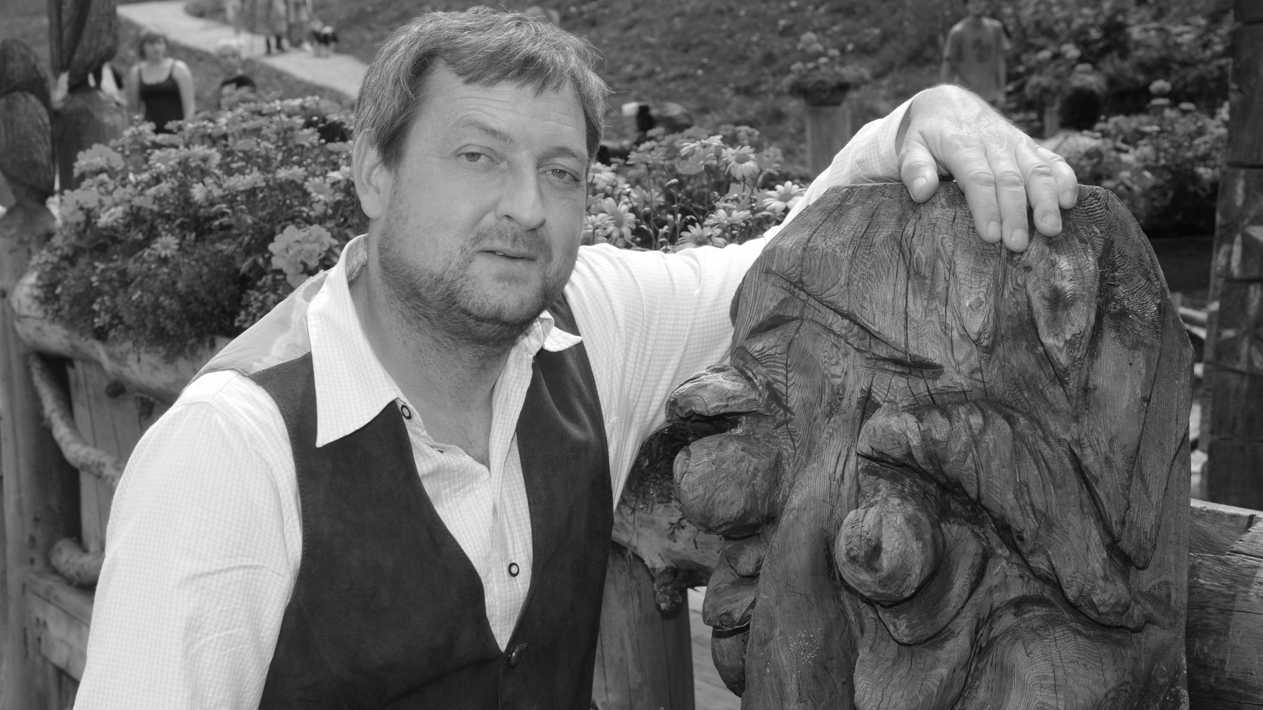 Der Schauspieler Maximilian Krückl neben einer Holzfigur