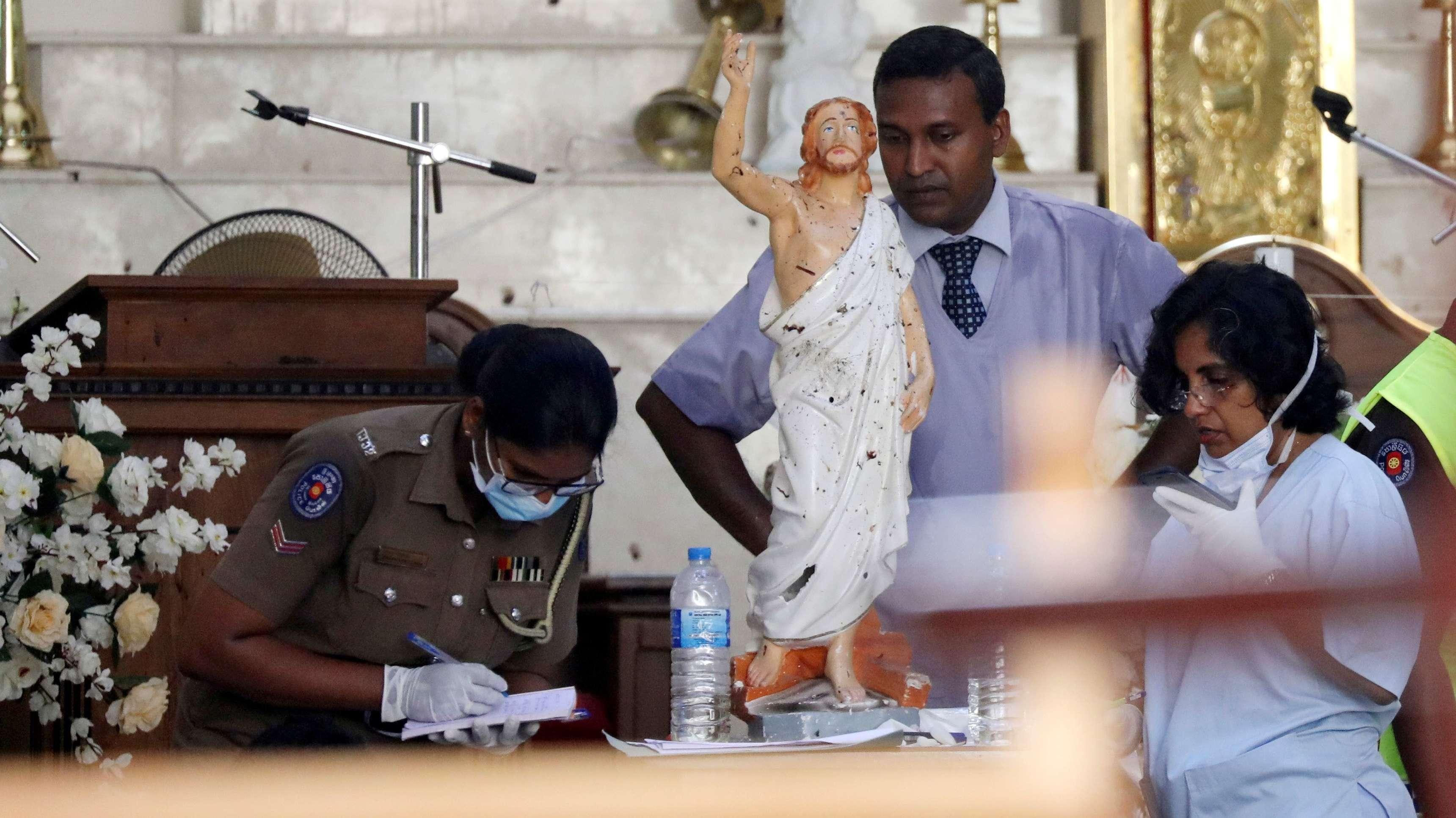 Polizisten stehen neben einer Jesus-Statue in der verwüsteten St. Sebastians-Kirche in Negombo