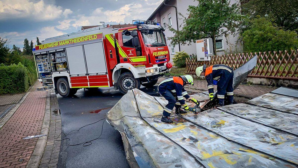 Feuerwehrleute im Einsatz an einem beschädigten Flachdach-Blech