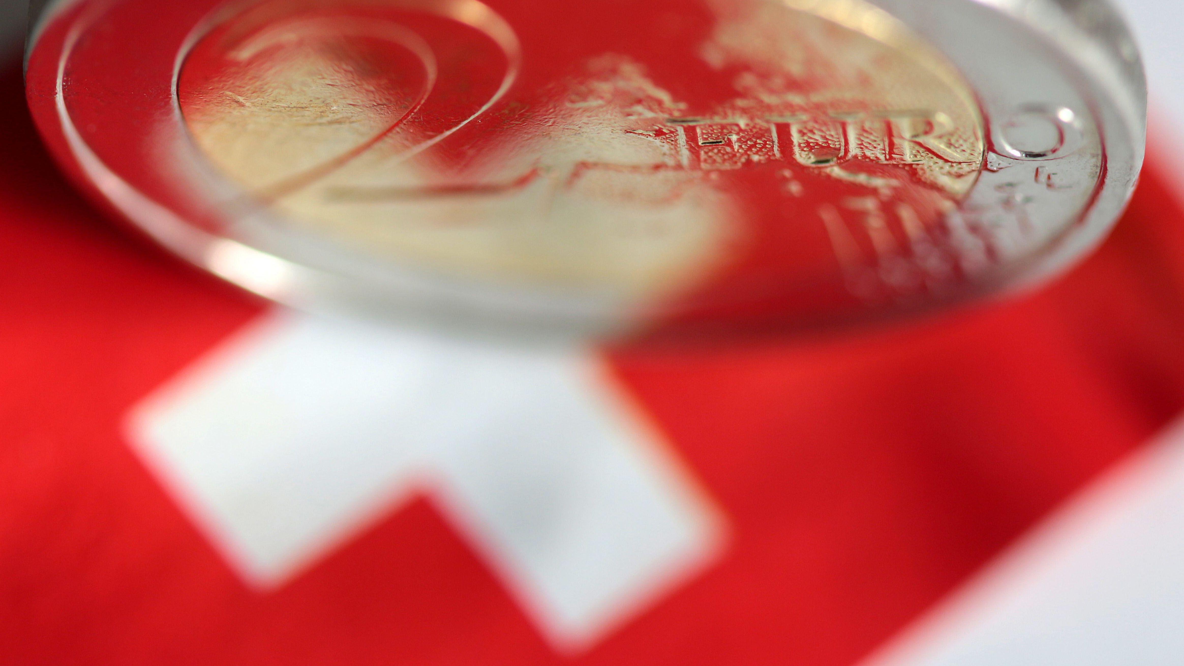 Eine Schweizer Flagge mit einer 2-Euro-Münze als Symbolbild.