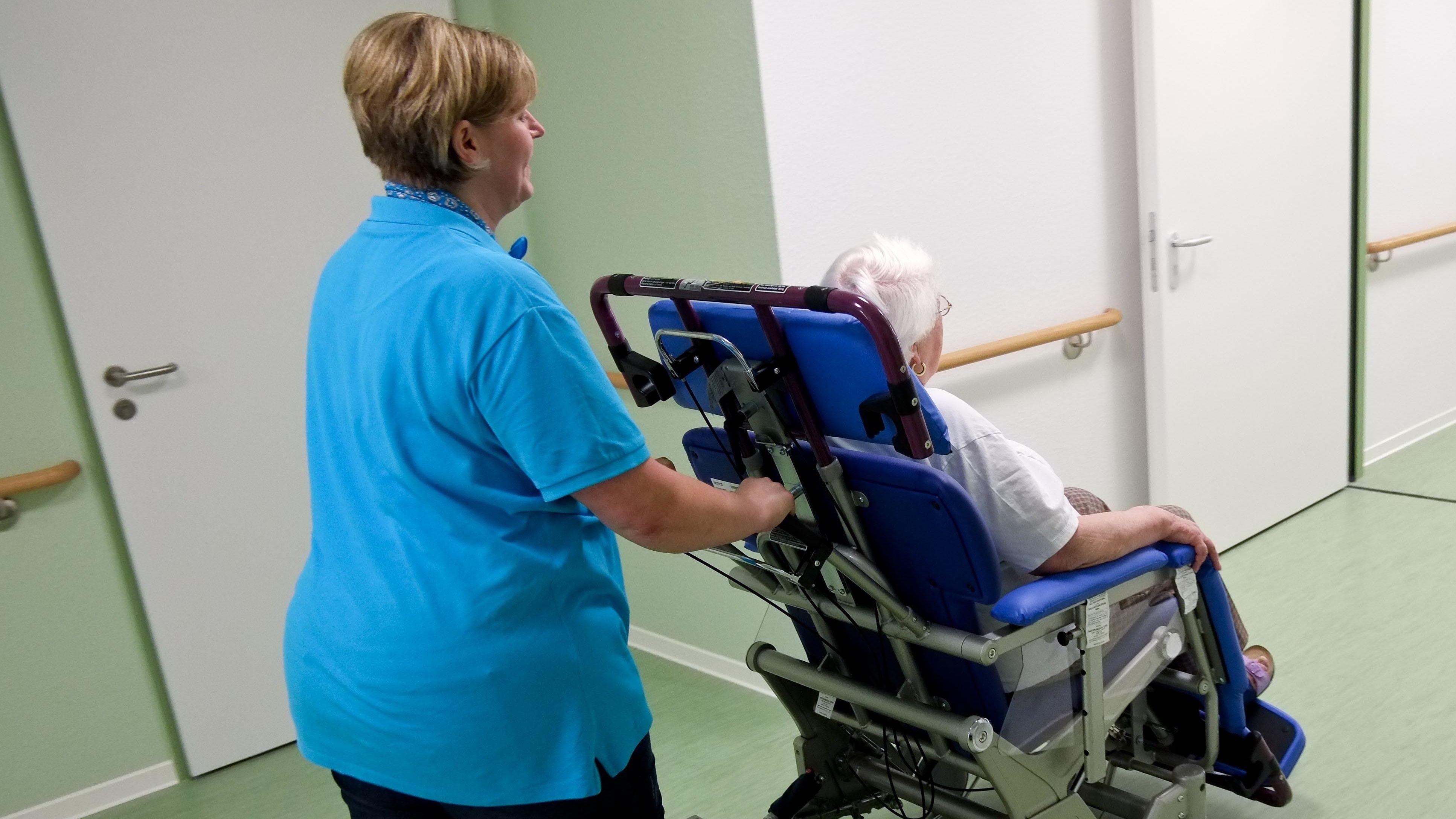 Eine Frau wird in einem Pflegeheim durch den Gang geschoben