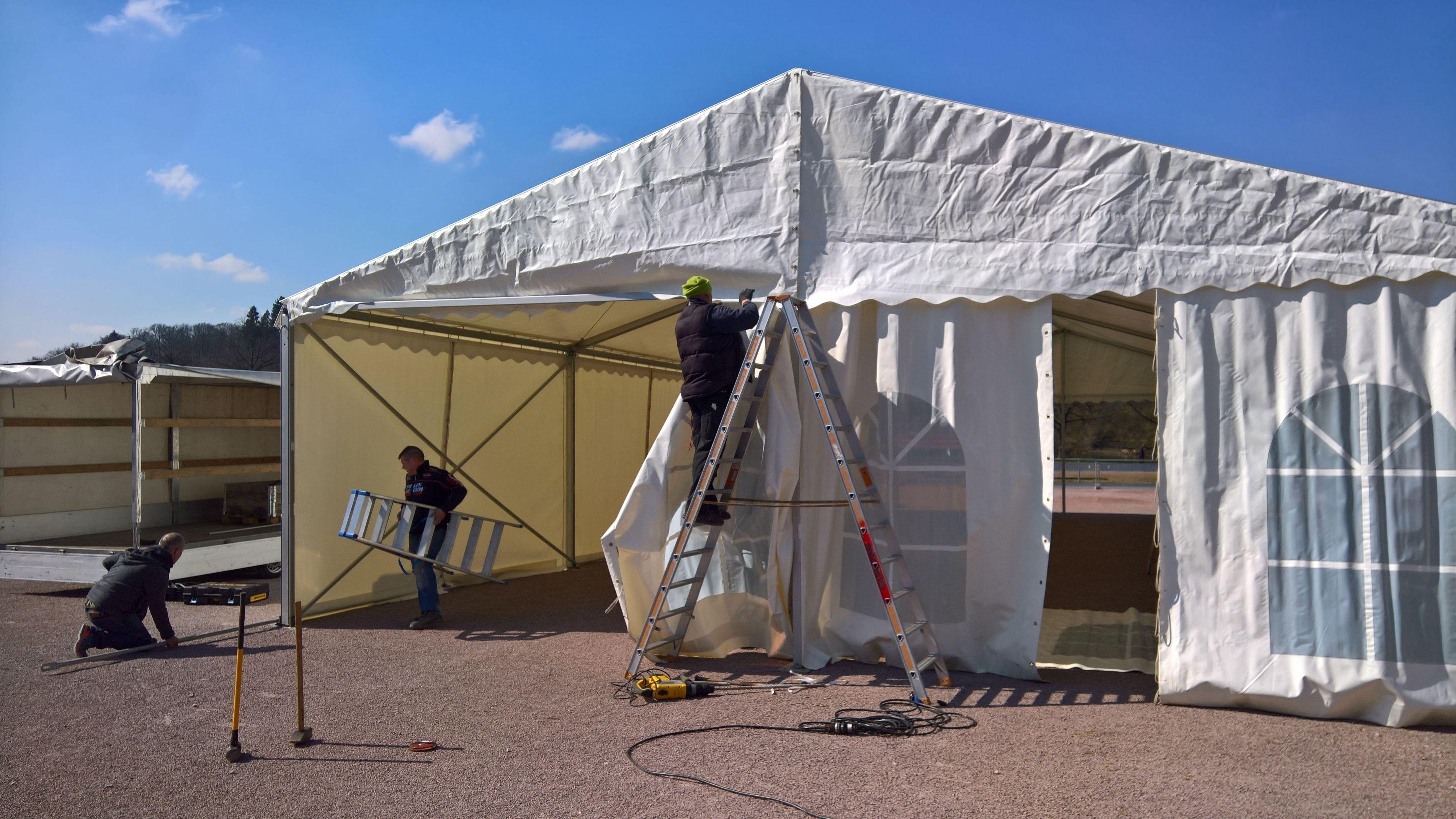 Männer bauen in Marktheidenfeld ein Zelt für die neue Corona-Teststrecke auf.
