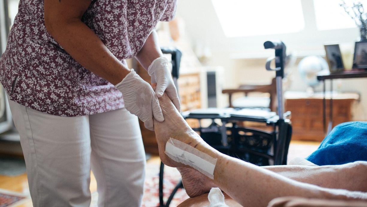 Pflegekraft versorgt Fuß einer alten Dame