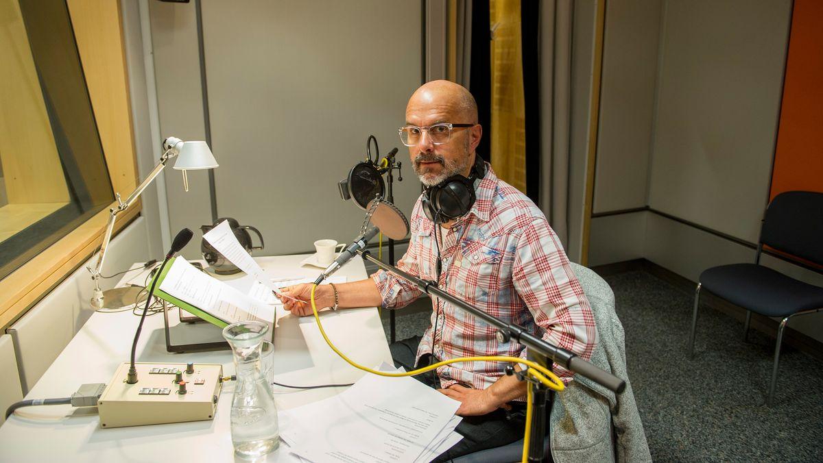 Christoph Maria Herbst in kariertem Hemd vor einem Mikrofon im BR-Studio