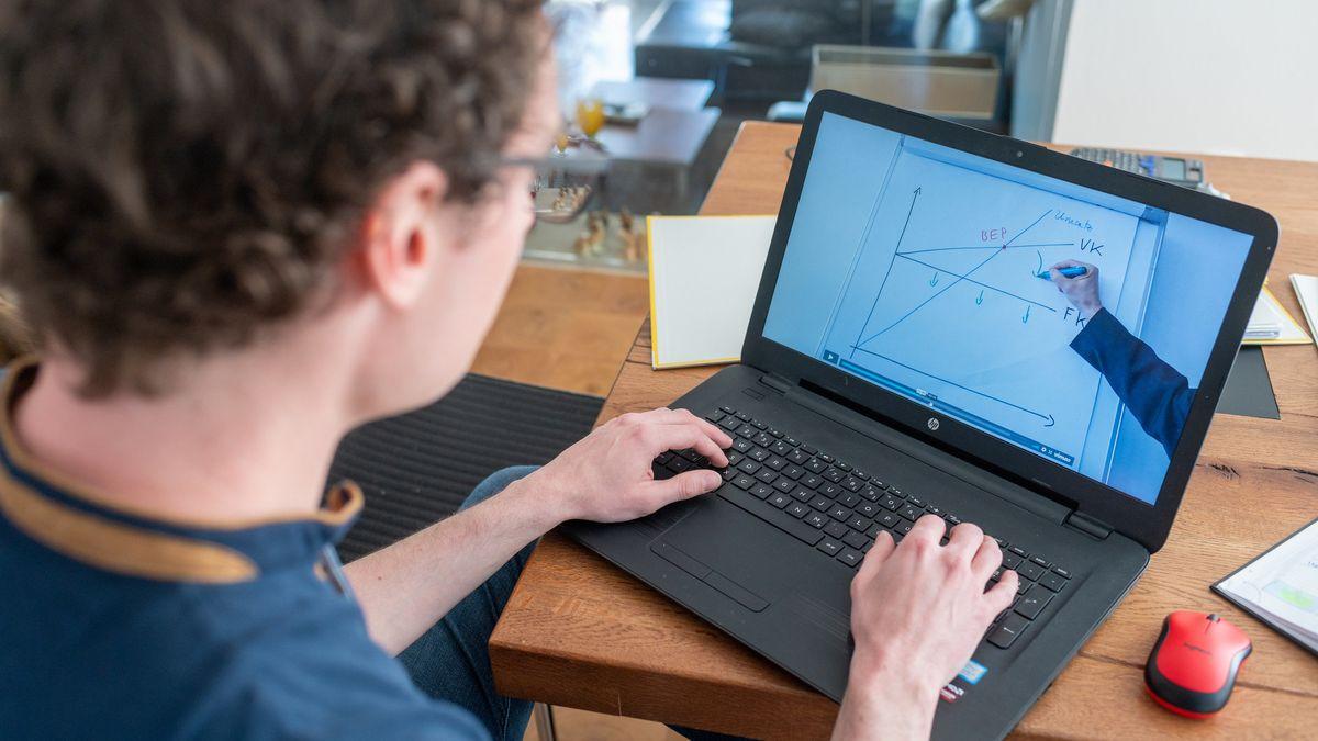 Ein Student sitzt zu Hause vor einem Laptop, auf dem ein Erklärvideo seiner Universität läuft.
