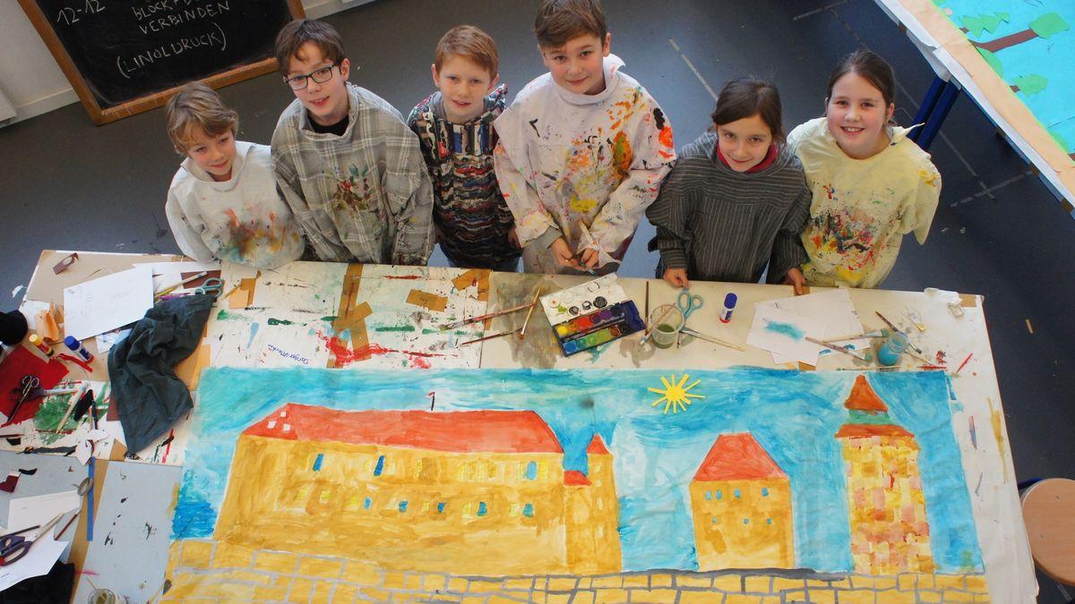 Kinder in Malkitteln vor ihrem Bild von der Nürnberger Burg.