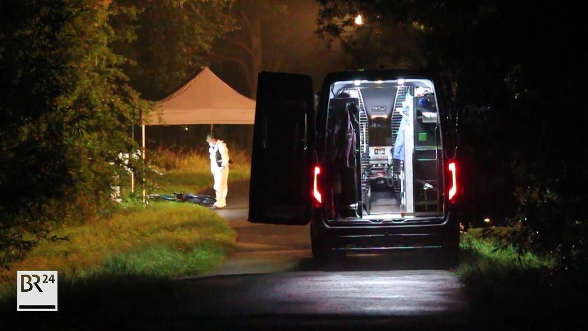 Auf einem Radweg parkt nachts ein Einsatzfahrzeug der Polizei, dahinter ein Zeltdach, unter dem ein Ermittler im weißen Schutzanzug steht.