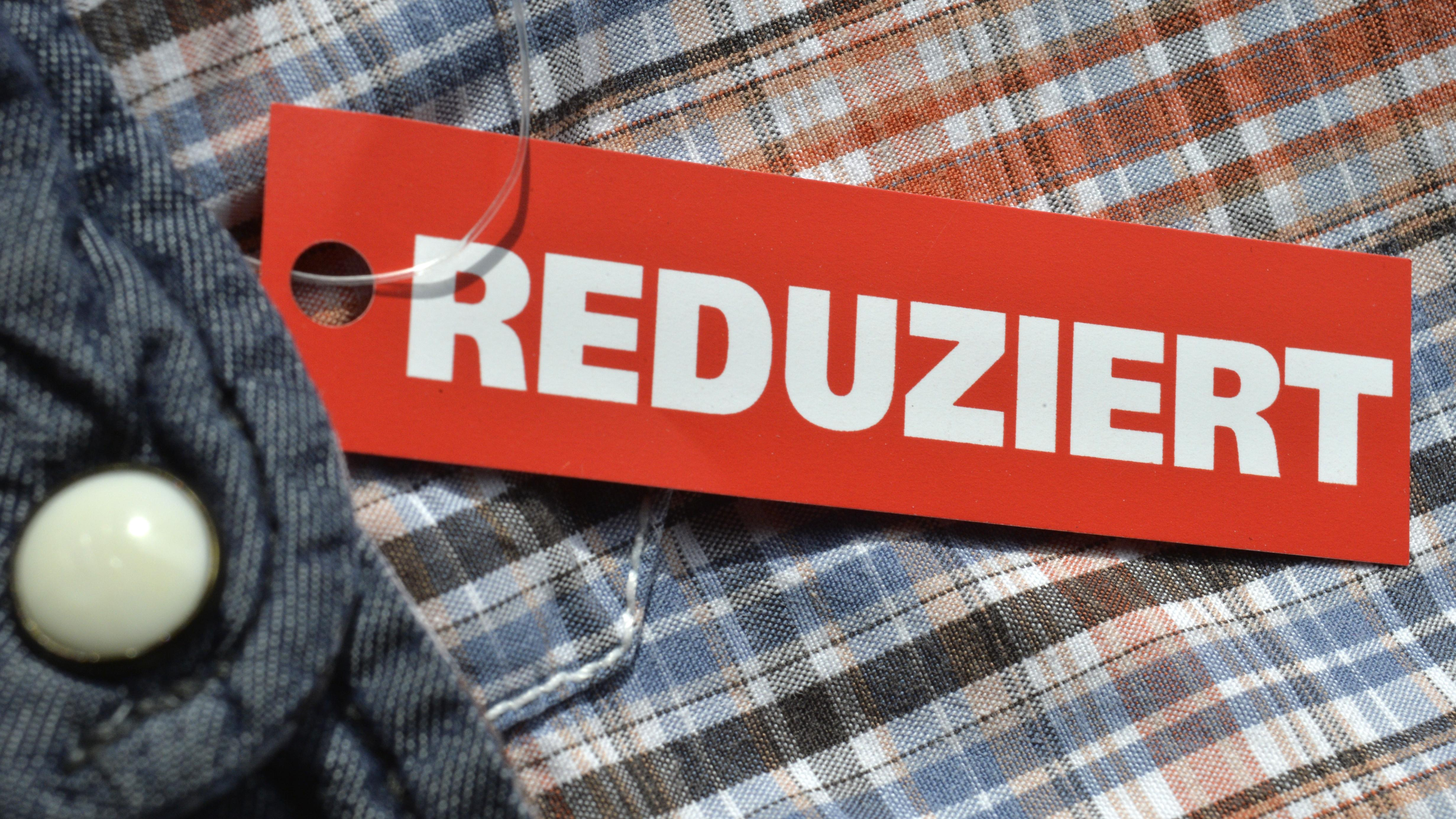 """Schild mit Aufschrift """"Reduziert"""" liegt auf Kleidungsstück"""