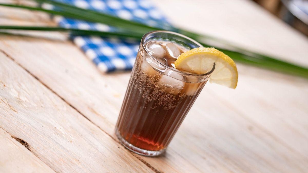 Ein Glas Cola-Mix-Getränk auf einem Holztisch
