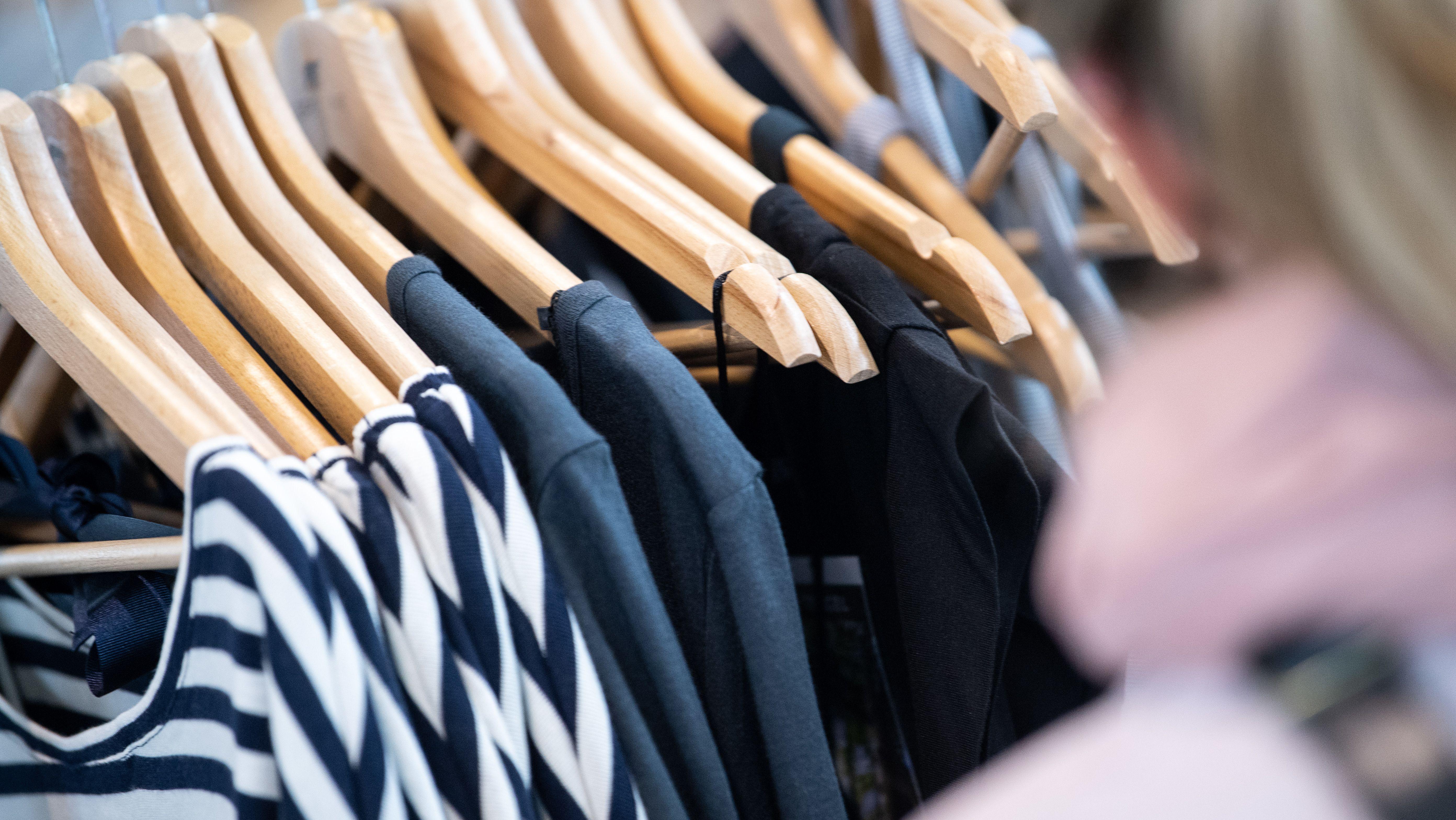 Klamotten hängen auf Kleiderbügeln an einer Kleiderstange.