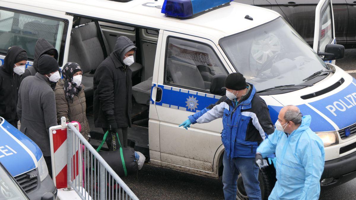 Eine Gruppe der aufgegriffenen Flüchtlinge steigt in Polizeitransporter.