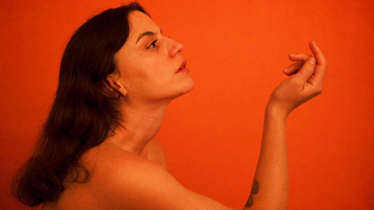 Sängerin Angel Deradoorian sitzt vor einer orangen Wand. Man sieht sie im Profil, oberhalb der Schulter, sie ist nackt.  Sie blickt auf ihre Hand, die sie in einer Pose gehoben hat.