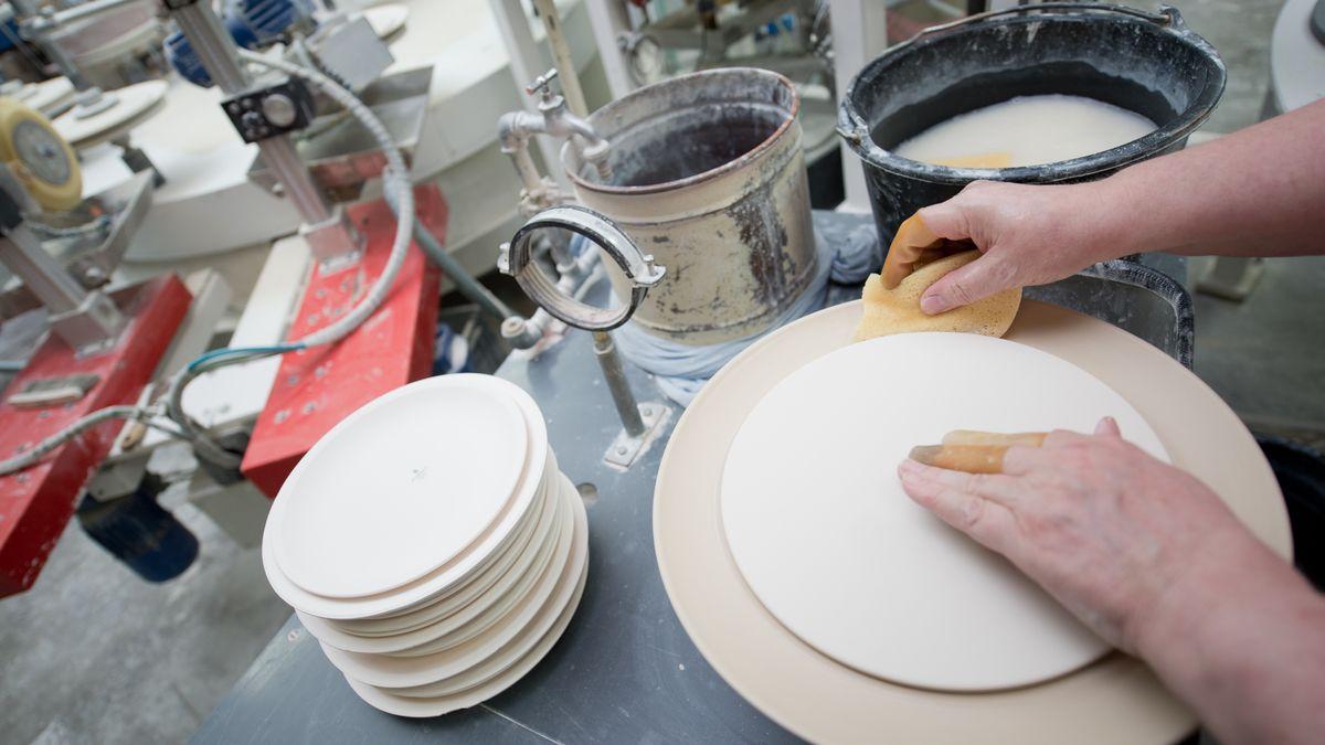 Eine Mitarbeiterin glättet in der Produktion der Porzellanfabrik BHS tabletop in Schönwald im Landkreis Wunsiedel die Kanten eines ungebrannten Tellers mit einem Schwamm.