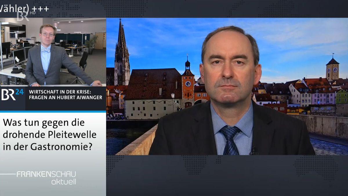 Hubert Aiwanger schaut in die Kamera, im Hintergrund die Stadtsilhouette von Regensburg.