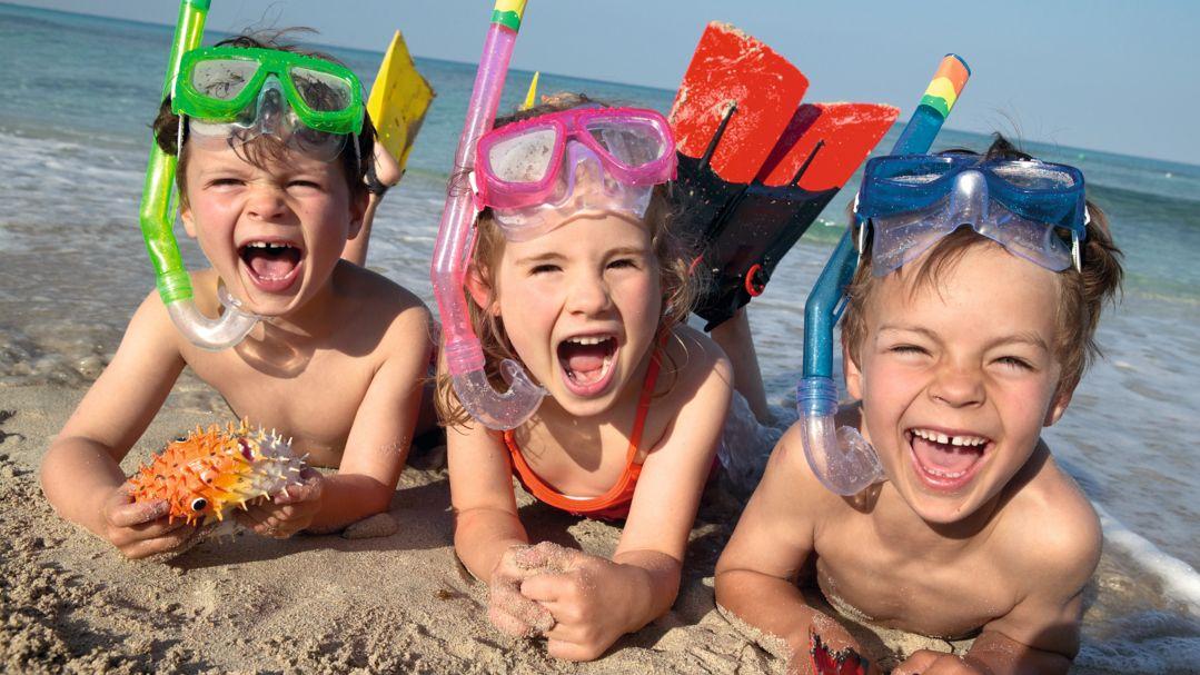 Drei Kinder mit Taucherbrillen und Schnorchel am Strand.
