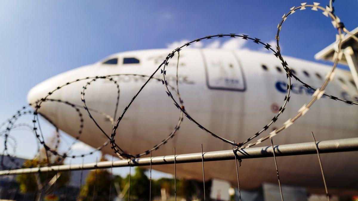 Ein Flugzeug steht hinter einem Stacheldrahtzaun