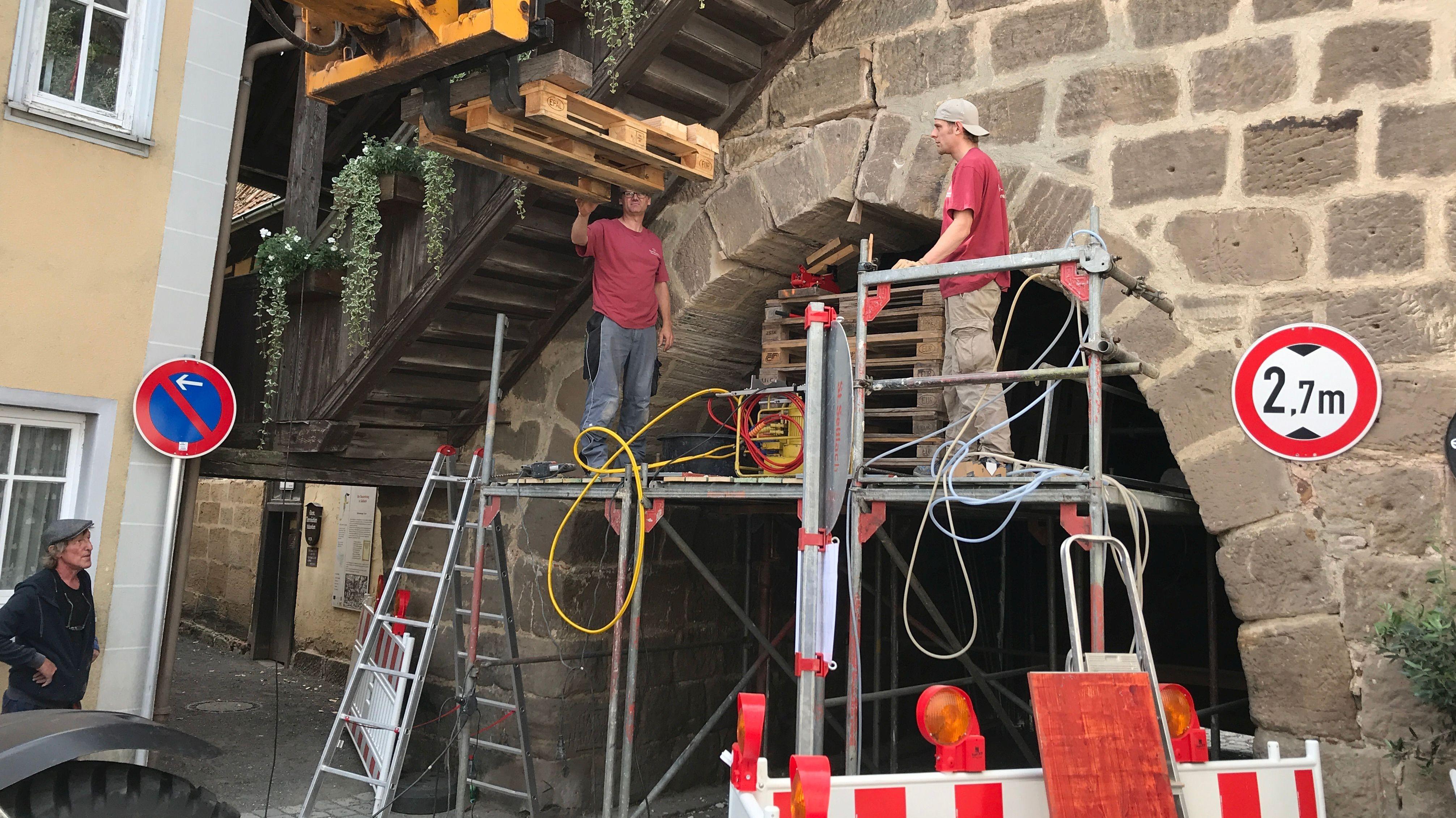 Zwei Bauarbeiter stehen auf einem Gerüst vor dem Rothenburger Tor in Seßlach.