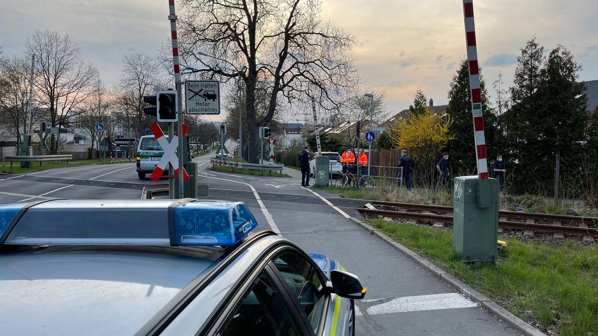 Mehrere Polizeibeamte stehen nahe des Bahnübergangs, das rote Fahrrad des Opfers ist zu sehen.