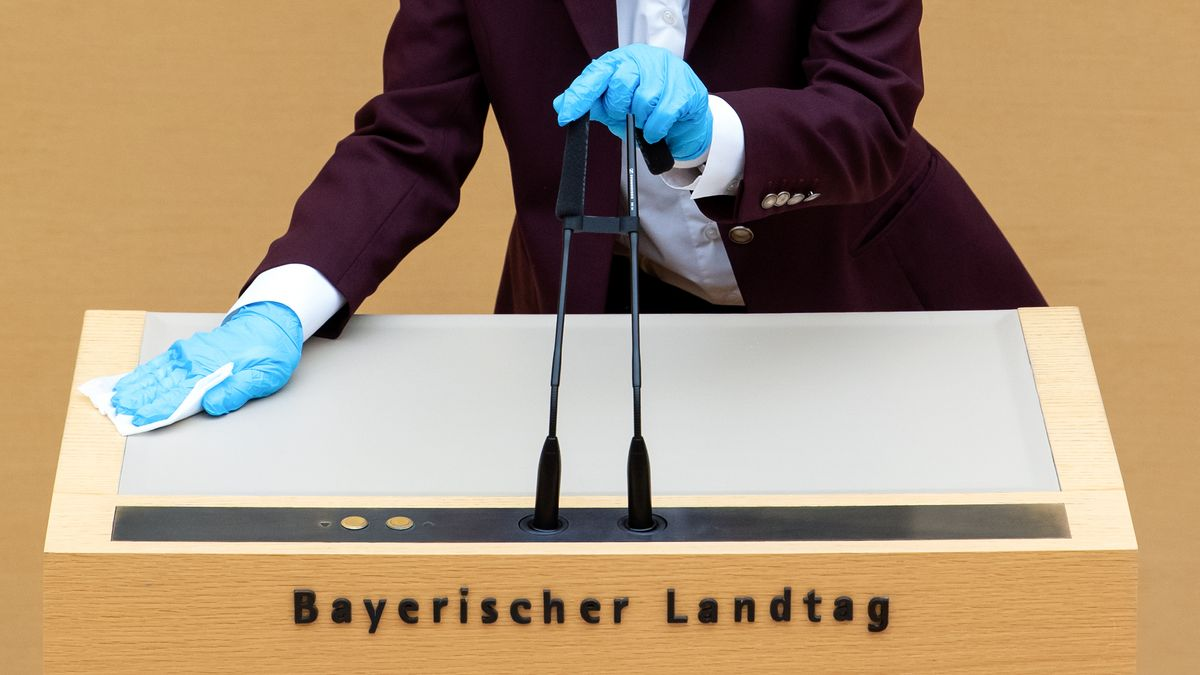 Eine Mitarbeiterin des bayerischen Landtags desinfiziert das Rednerpult und die Mikrofone.