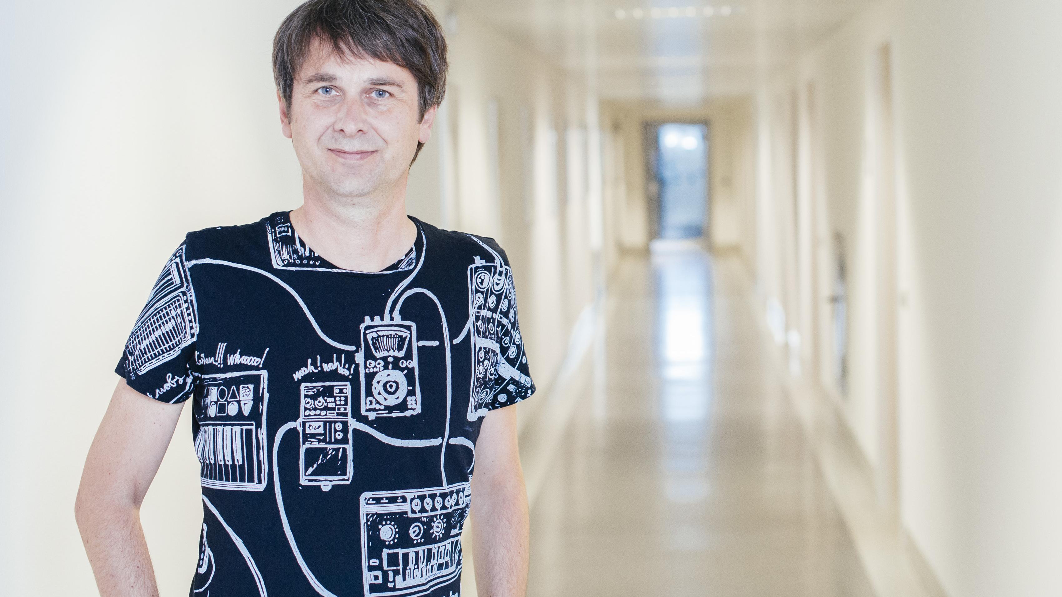 Martin Zeyn, Leiter des Nachtstudios auf Bayern 2 im T-Shirt in einem hellen Gang des BR