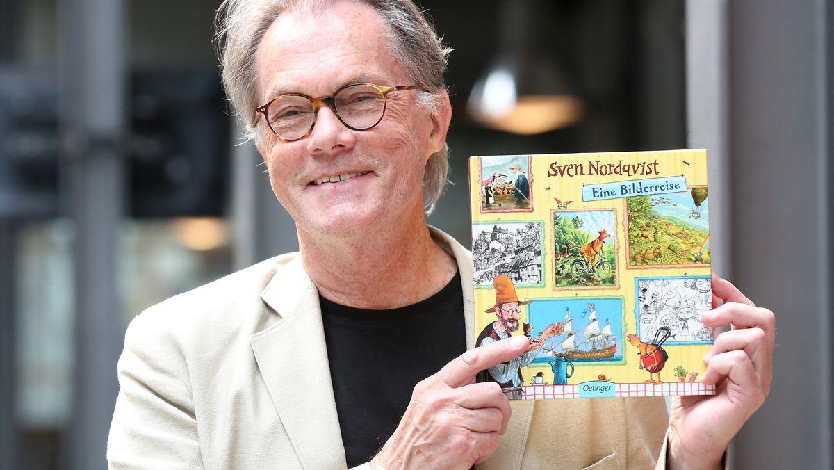 """Sven Nordqvist hält lächelnd eines seiner """"Petterson und Findus""""-Bücher hoch"""