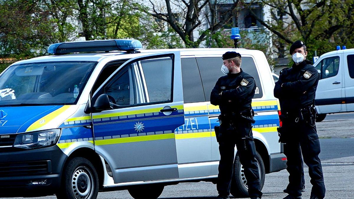Polizeibeamte vor einem Streifenwagen