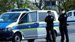 Polizeibeamte vor einem Streifenwagen   Bild:News5