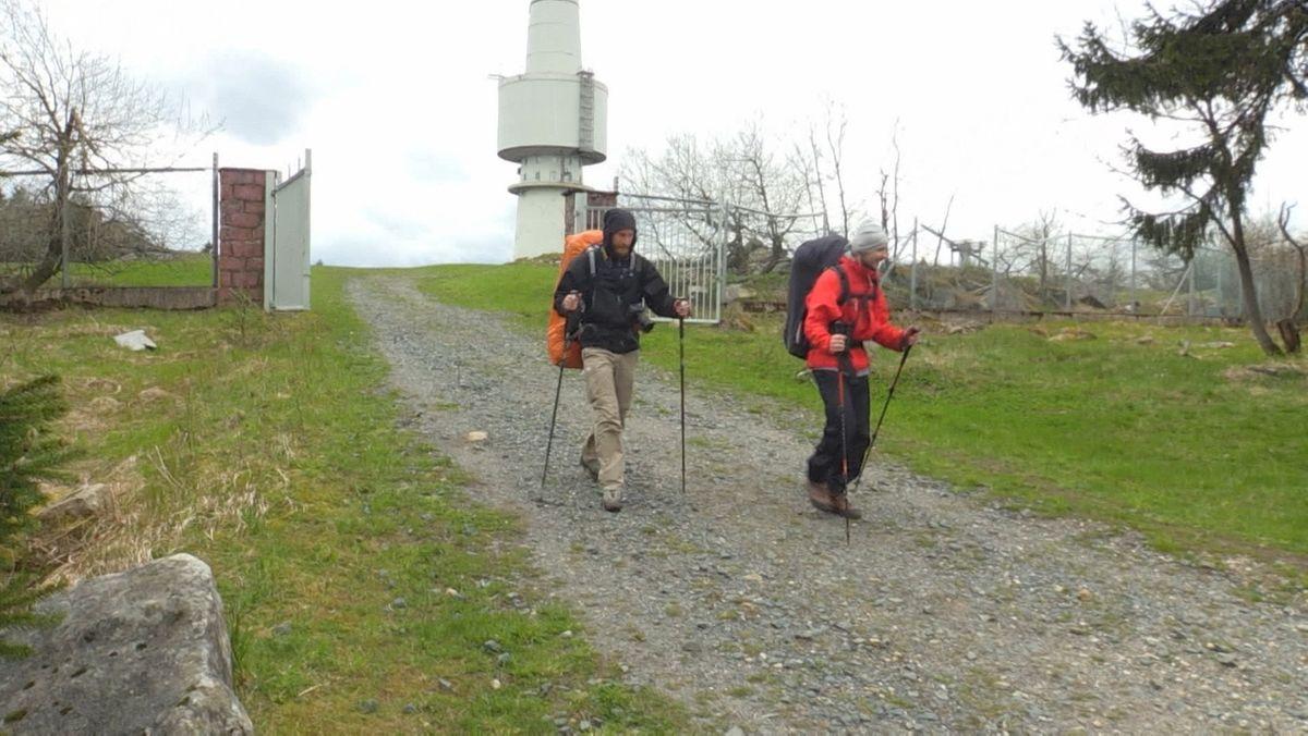 Zwei Männer wandern auf dem Schneeberg, im Hintergrund ein Turm.